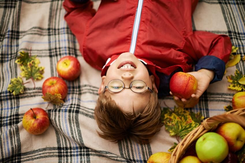 little boy lying on blanket rounded by leafs and apples