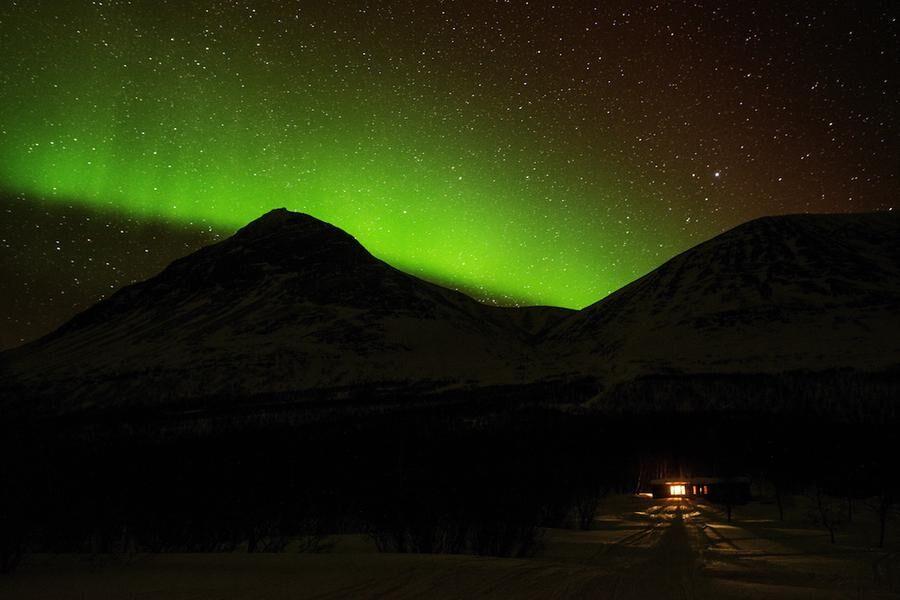 MAGISKT LJUS Norrskenet lyser upp himlen över den lilla fjällstugan.