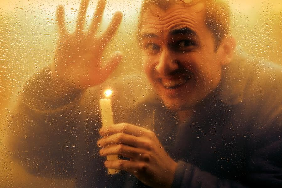 Man with a candle looking through the window