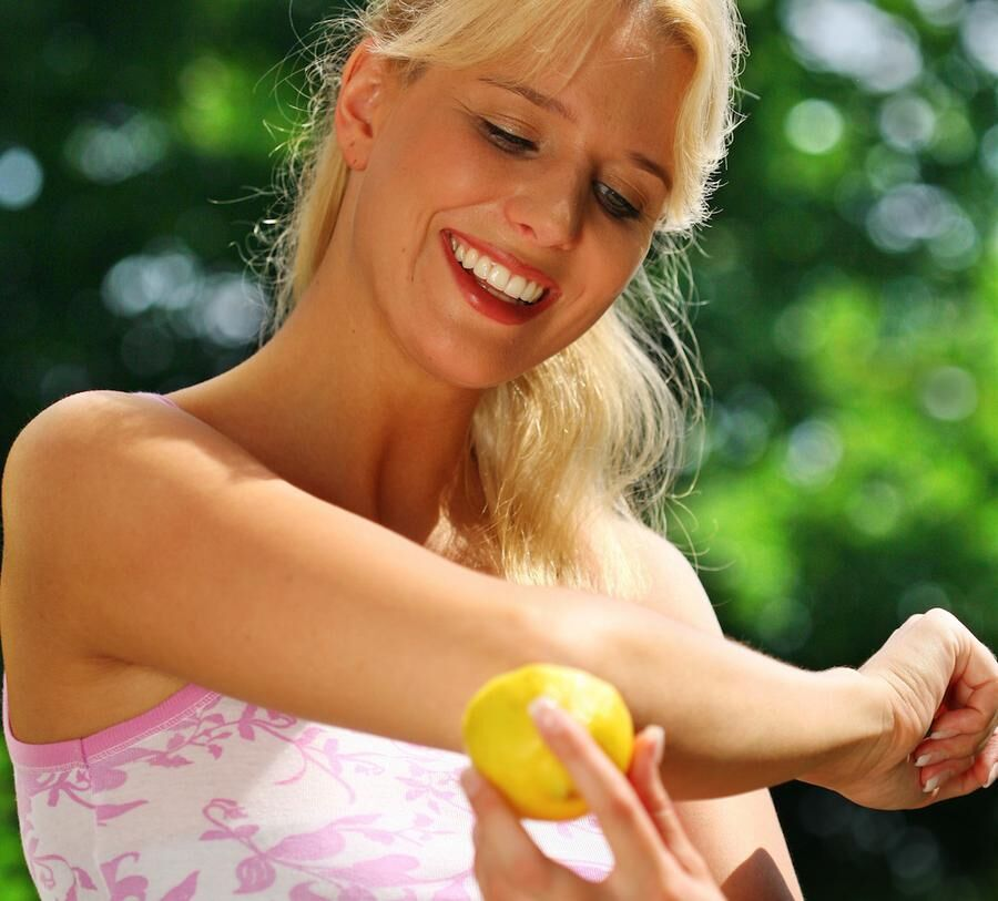 woman rubs the elbow with a lemon