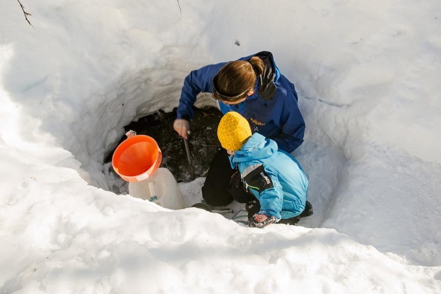 Vattenhämtning. Från en öppen källa i snön fyller mamma Annika och sonen John vattendunkarna.