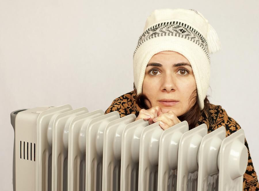 Young woman near a heater