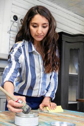 Nicole renoverar ett stort köksbord.