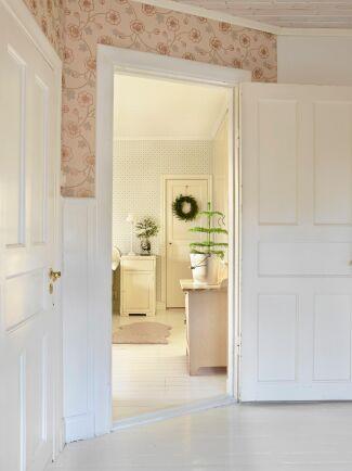 Det gamla trägolvet i hallen togs fram och målades vitt och gammeldags tapeter sattes upp.