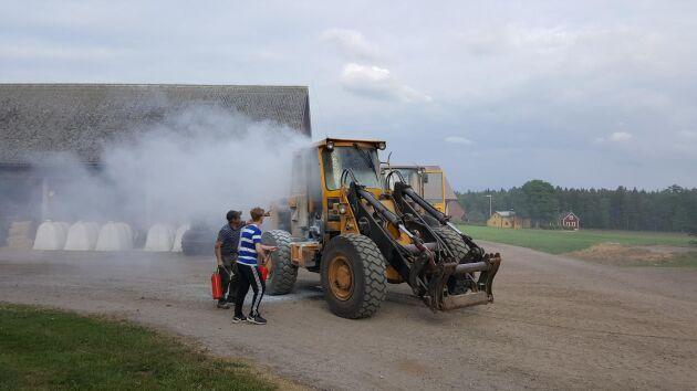 Lars Karlsson och sonen Isidor slutför släckningsarbetet. Det var i torsdagskväll som den gamla hjullastaren började brinna i en lada på familjens gård.