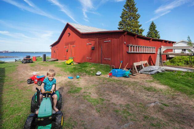 På gården finns stora ytor för barnen att leka på. Hubert älskar att köra traktor. Bakom syns är sjöboden.