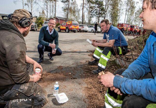 Inrikesminister Mikael Damberg samtalar med Peter Svensson, Johan Svensson och Robin Persson, som hjälper till med skogsbrandsläckningen utanför Hästveda.