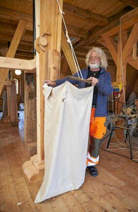 Ulf visar hur det nymalda mjölet ska rinna ned i rena jutesäckar.
