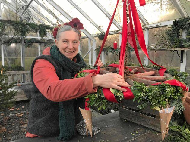 Marie binder en fin krans med granris och lingonris från skogen dekorerad med pappersstrutar och röda sidenband.