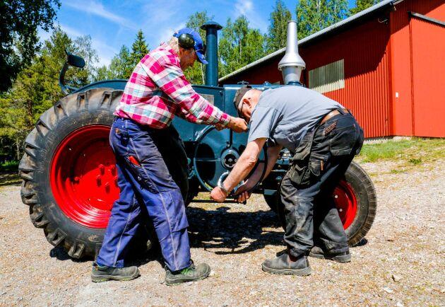 Vincent Johansson och Mats Torstensson vevar igång motorn med traktorns ratt.