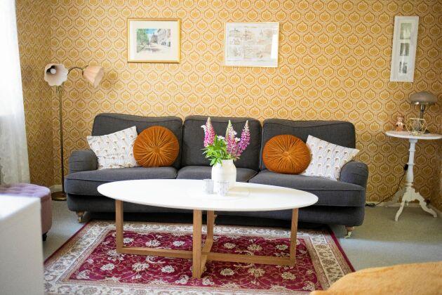 Vardagsrummets soffa och soffbordet är nyköpta, resten är arvegods eller loppisfynd. Paret ser numera den gula tapeten som en utsmyckning.