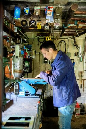 Markus slipar en yxa inne i den rikligt utrustade verkstaden.