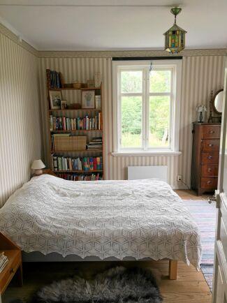 """Kammaren bakom köket är mormor Margaretas rum. Vid huvudändan av sängen satt tidigare en dörröppning. """"Det var omöjligt att möblera kammaren med två dörrar och två fönster och dessutom blev köket nu dubbelt så stort tack vare den nya väggen"""", säger Lovisa."""
