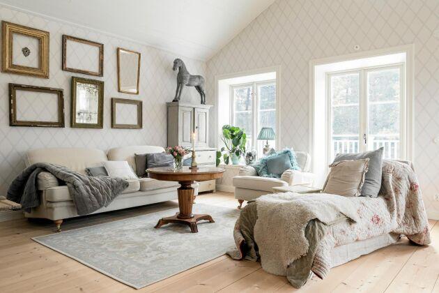 Rymden och takhöjden i vardagsrummet ger möjlighet till att vara lite lekfull och bygga på höjden. Som den antika trähästen ovanpå det gamla skåpet.