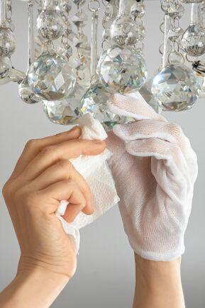 En gammal kristallkrona putsas för hand.