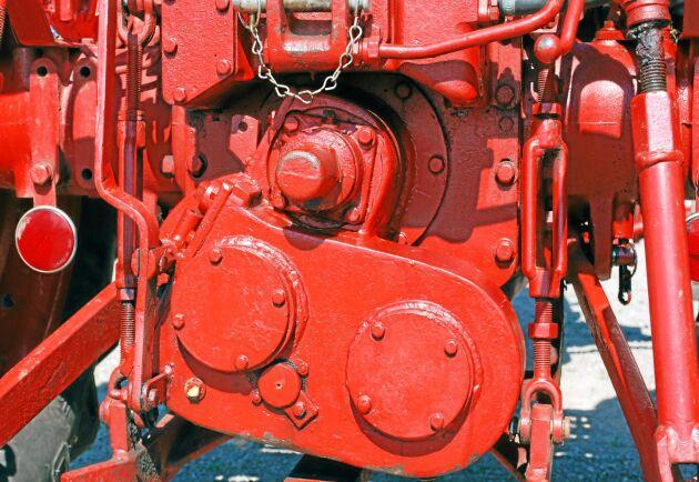 Kraften till framaxeln tas ut från kraftuttaget. Remmar överförde kraften från början men nu är det kugghjul innanför locken.