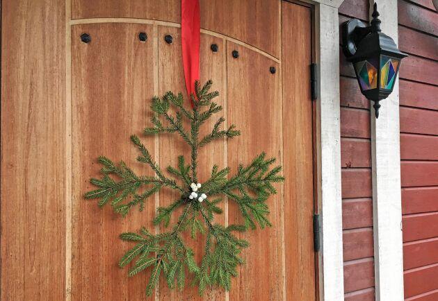 En grön flinga av granris till ytterdörren.