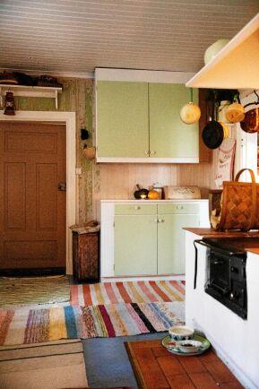 Vedspisen sprider värme och de gamla kökskåpen har fått ny, mild grön färg.