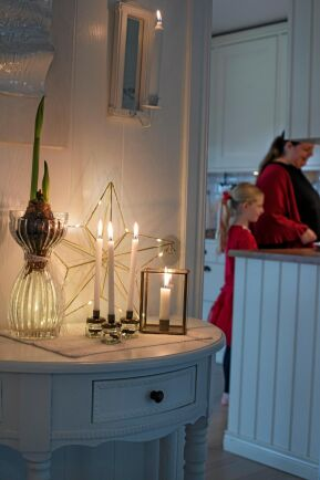 Levande ljus på hallbordet ger mysig stämning.