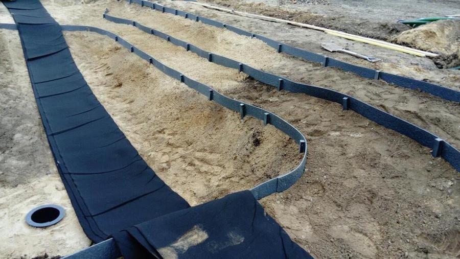 De flesta av väljer en damm med naturligt sluttande sidor. Här ser man bottenavloppet i den djupaste delen och kantband som ska hålla stenarna som ska täcka botten på plats. Foto: Dammcenter.