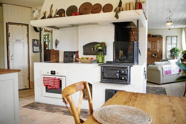 Som vägg mellan kök och vardagsrum har Helena låtit mura upp en bred murstock med öppen spis på vardagsrumssidan och vedspris i köket.