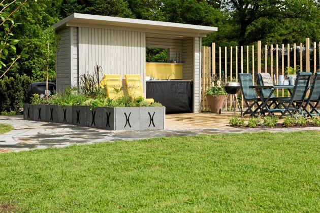 När trädgårdsmästaren Bo Rappne designade en lättskött trädgård blev det här uteköket en del av det. En liten bod med skjutdörr döljer diskbänk och förvaring.