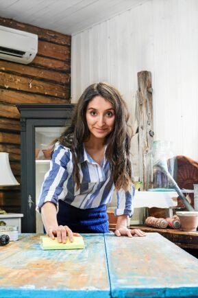 Här slipar Nicole ett gammalt köksbord i sin studio/verkstad.