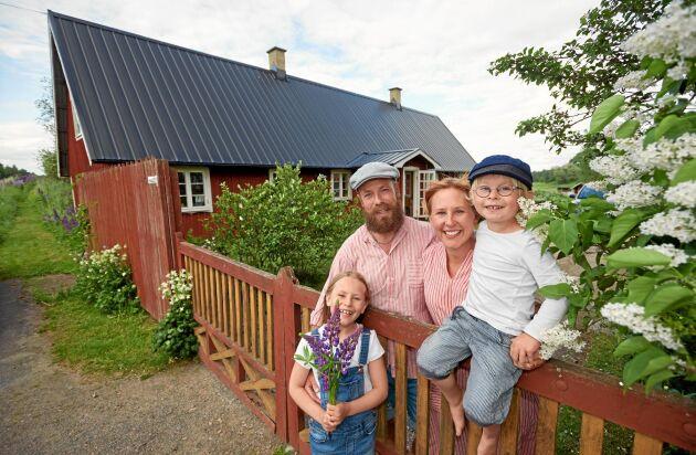 David och Lella Ernstedt och deras två barn Vendeli och Atle framför sitt ovanliga boende – i en backstuga.