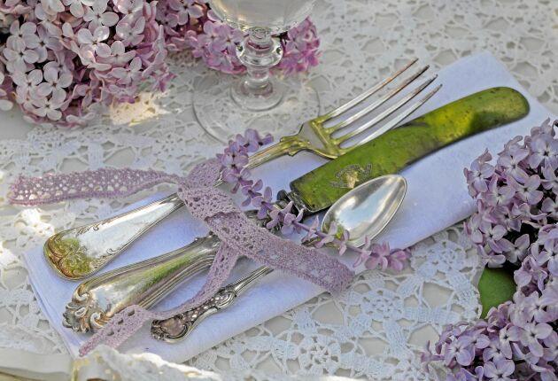 Ett litet dukningstips som höjer stämningen vid bordet är lite udda bestick från loppisen på en linneservett och det hela hålls ihop med spetsband och en ring av syrenblommor.