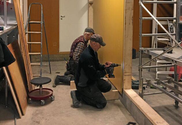Henriks pappa Rikard Ahlsten och medarbetaren Göran Westberg arbetar med utbyggnaden av hönshuset.
