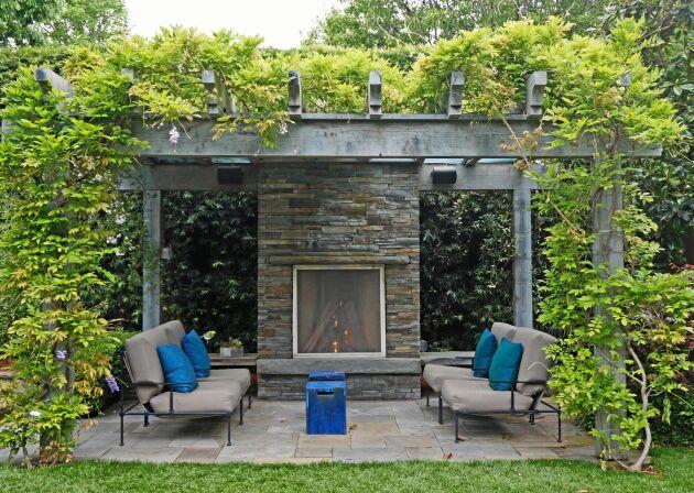 Grånad pergola mitt i trädgården. Här med en öppen spis att värma sig vid.
