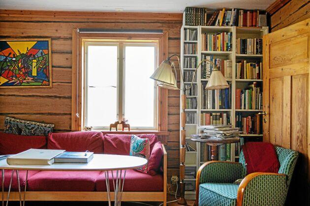 Vardagsrummet med timrade väggar och mycket litteratur om jordbruk och miljö.