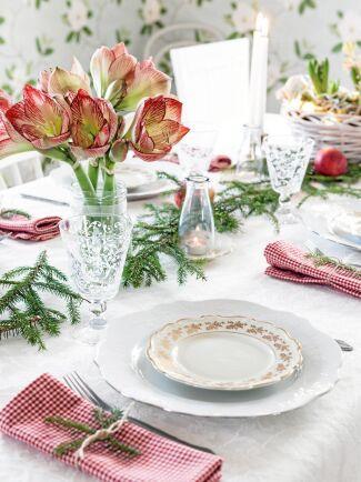 Dukat för julkalas med amaryllis, granris, finporslin och rödrutiga linneservetter.