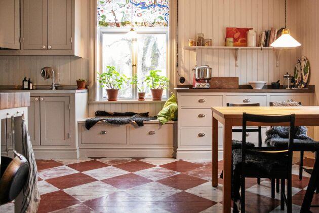 Rutmålat trägolv och platsbyggda skåp i det rymliga köket.