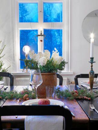 Anna har valt bort adventsstjärnor och elljusstakar i flera av fönstren och ersatt dem med ringar med levande ljus. På bordet står tulpaner, granris och äpplen.