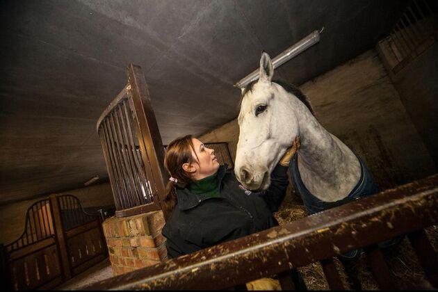 Elitryttaren Lisen Bratt Fredricson i stallet på Grevlunda gård med hopphästen Clarence.