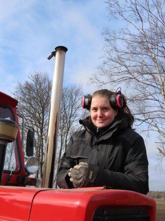 Ida Karlsson med veterantraktorn Volvo BM 650. Den går runt 100 timmar per säsong och sköts extremt noggrant.