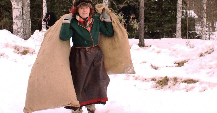 Vivi Sandström från Mora, en av förra årets forkörare bär två säckar som ska lastas på släden.