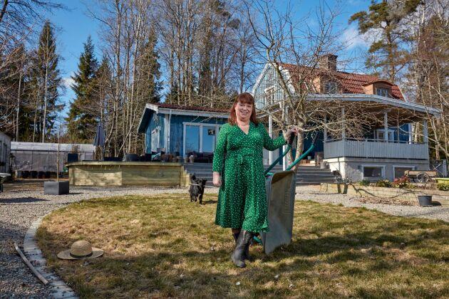 Johnna framför sitt hus på den sörmländska landsbygden med knoppande äppelträd i den sena våren.
