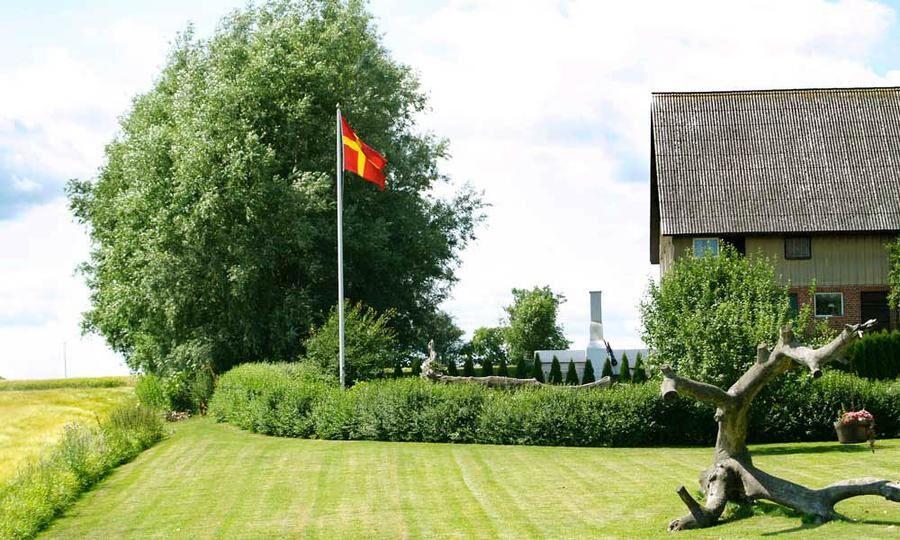 Den skånska flaggan vajar i vinden i värdshuset trädgård.