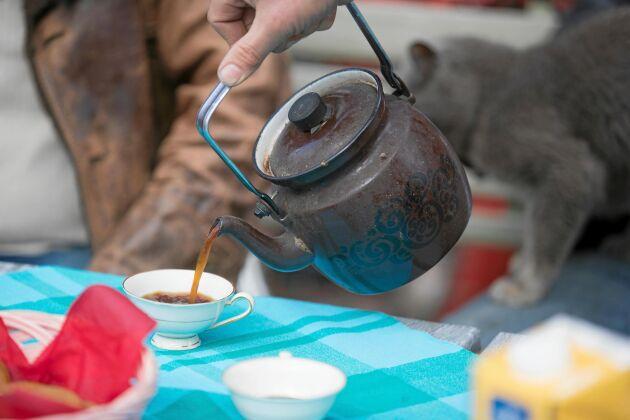 Leif Olofsson kommer ut med nykokt kaffe som han sedan serverar till sina gäster.
