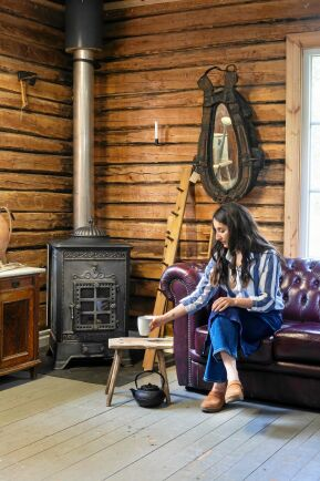 Nicole tar igen sig vid den gamla kaminen, som hon eldar med under vintertid för att kunna jobba i huset.
