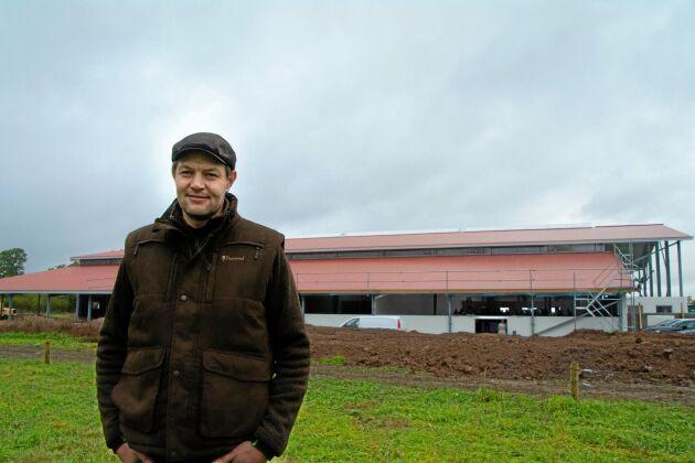 Anders Gunnarsson på Halla gård satsar mellan 30 och 40 miljoner kronor på mindre miljöpåverkan och högre djurvälfärd. Stallet i bakgrunden har plats för 3 520 grisar med möjlighet till utevistelse.