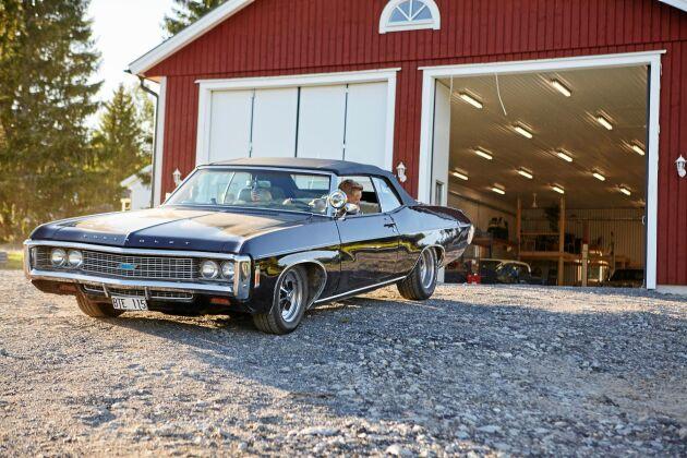 Gottfrid kör ut ur porten till det nybyggda garaget med sin svarta Chevrolet Impala 1969.
