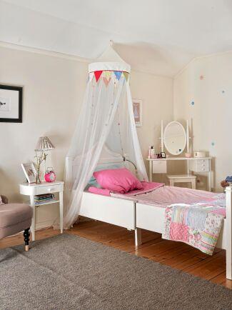 Dottern Tulias rum är en riktig flickdröm med antik utdragsäng och sänghimmel.