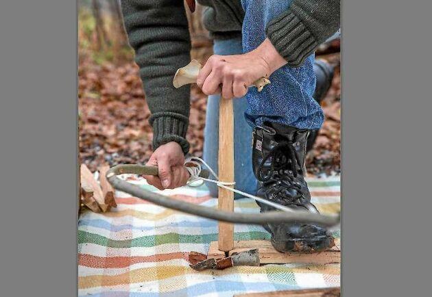 """För att få drillpinnen att rotera riktigt snabbt lindar Jonas bågsträngen – snöret – ett varv runt pinnen. Sen """"sågar"""" han så att friktion uppstår och kolpulver bildas och börja glöda."""