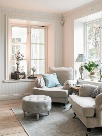 Sköna fåtöljer i en ljus hörna av vardagsrummet med extra höga fönster som släpper in mycket ljus. I fönstret står en fransk, antik kyrkoljusstake.