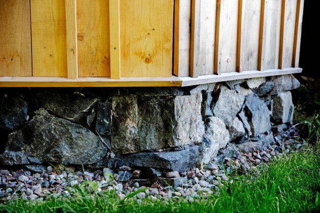 Kilsågad panel med lock ovanpå timrad laxknut som har lagts direkt på den nylagda stengrunden.