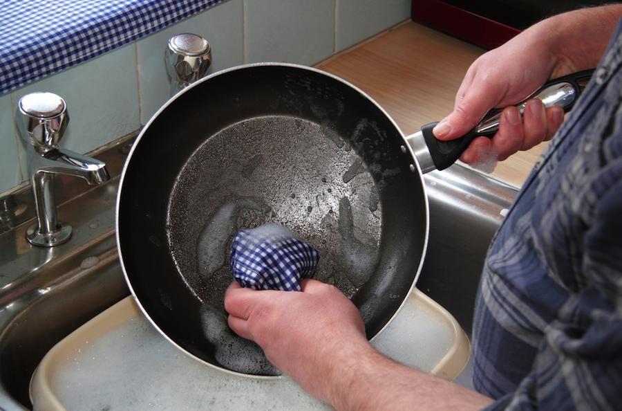 Man washing up pots/frying pan at a kitchen sink at home, England, UK
