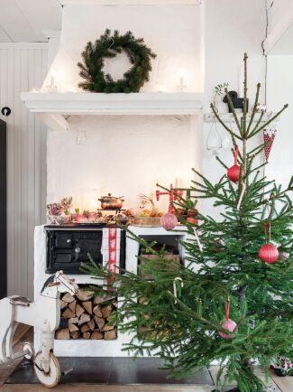 I hemmets hjärta finns denna underbara vedspis – men också en yvig julgran. Denna är enkelt utsmyckad med röda julkulor. Svårare än så behöver det inte vara.